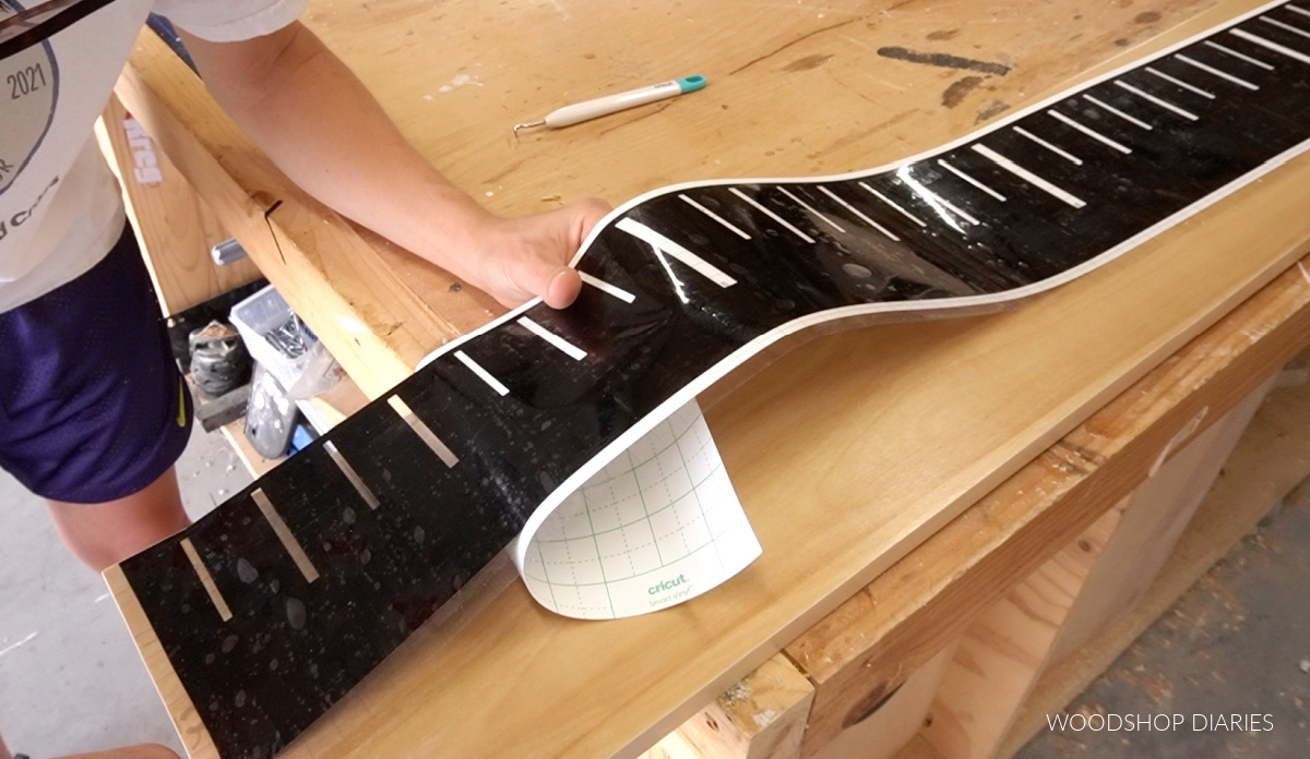 Vinyl stencil with ruler marks being applied to board at bottom edge