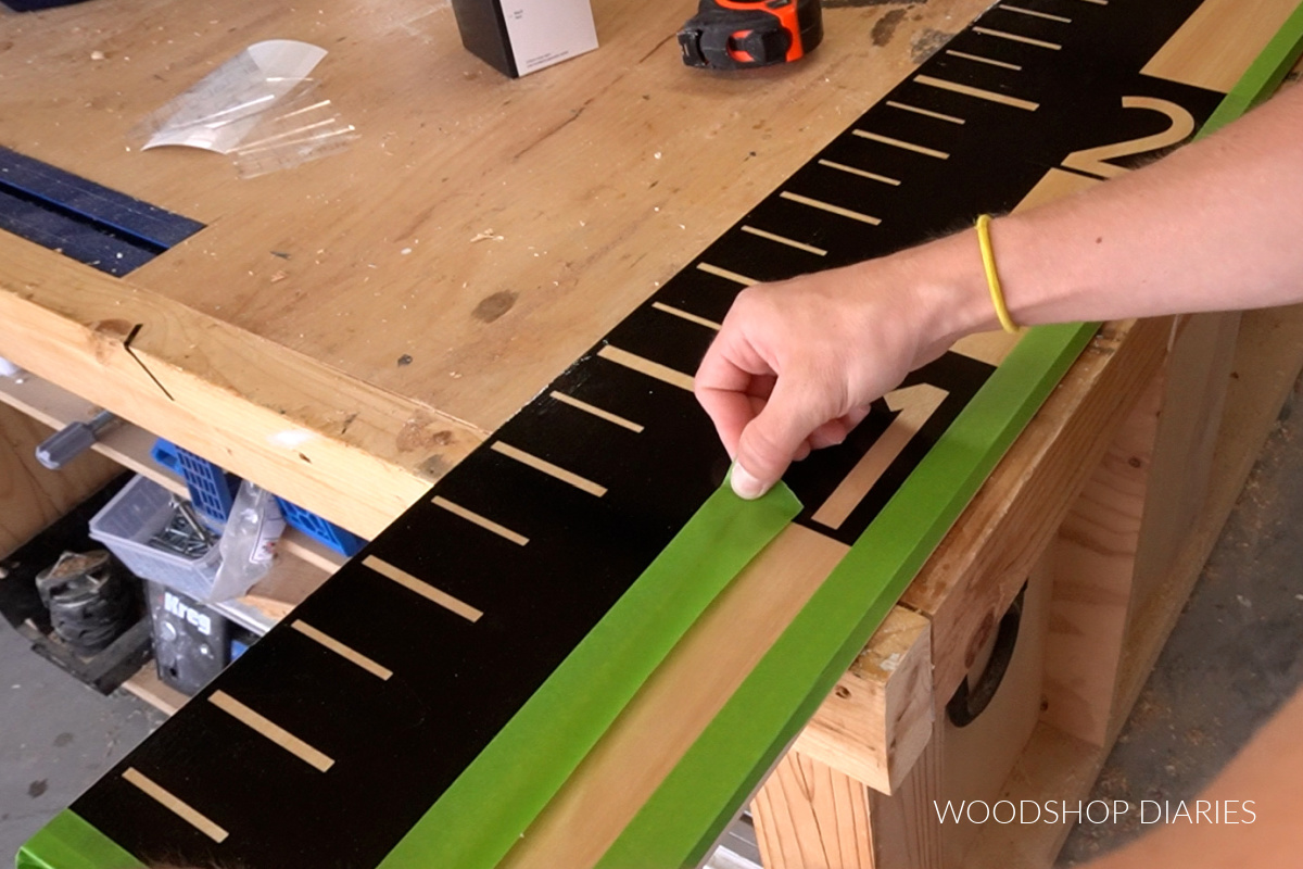 Applying painters tape to exposed wood before spray painting giant life size ruler board