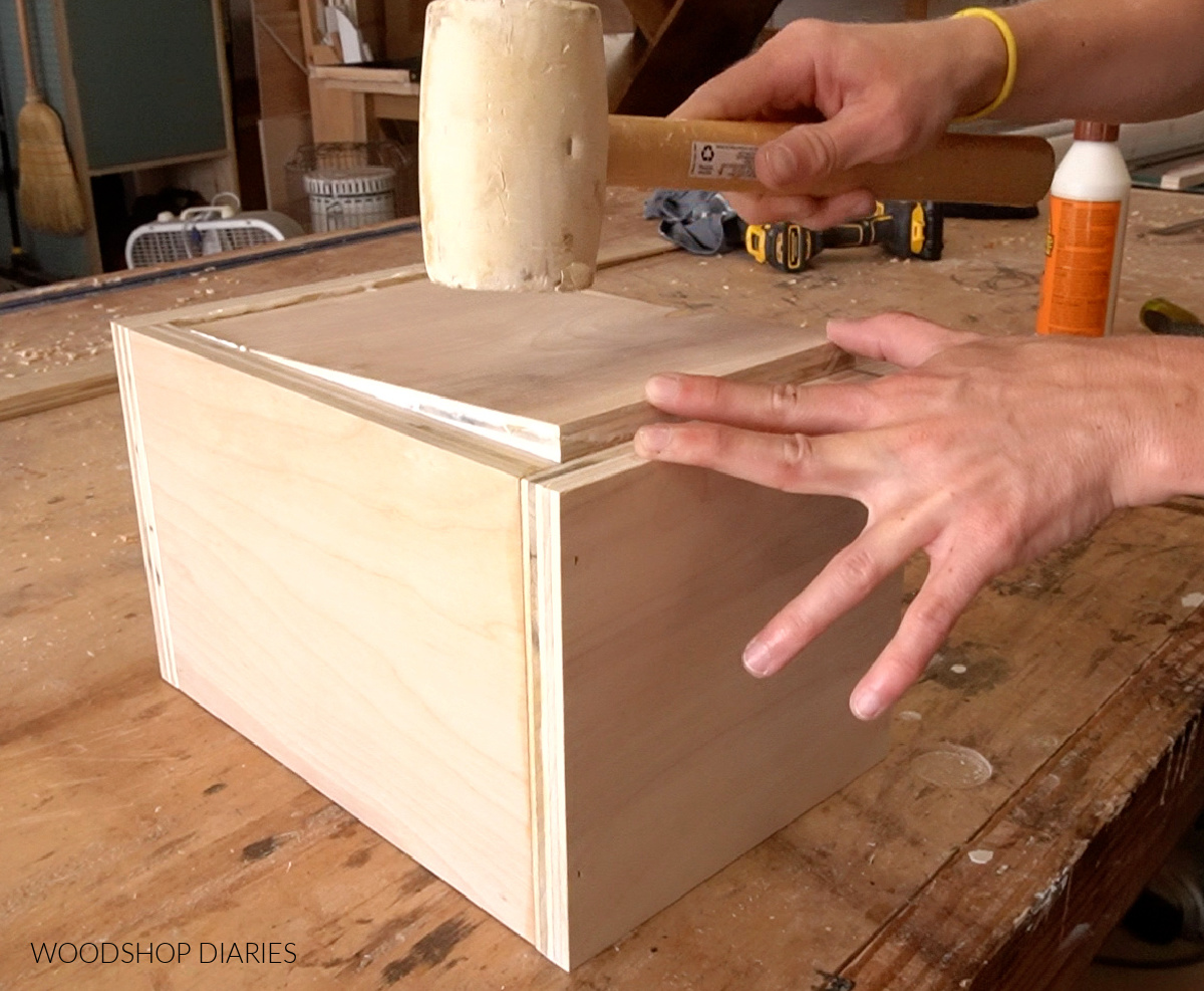 Using rubber mallet to tap bottom panel of scrap wood keepsake box in place