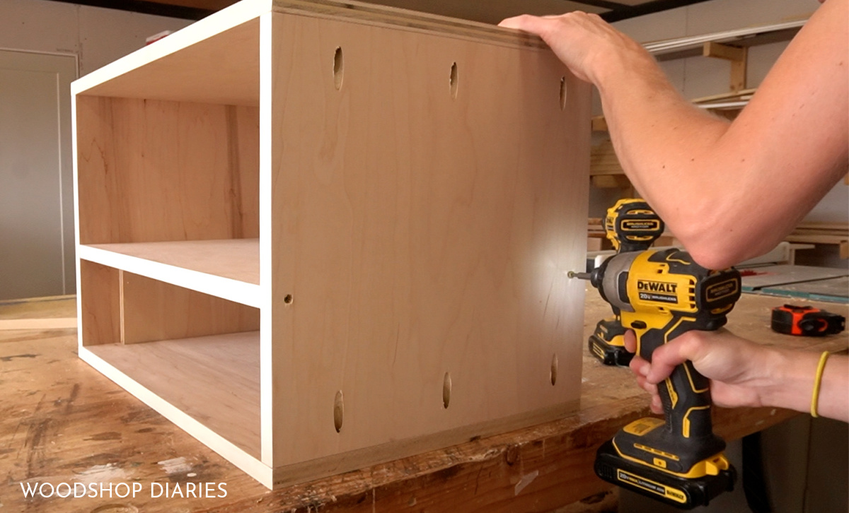 Shara Woodshop Diaries driving screws through side panels to attach shelf in place