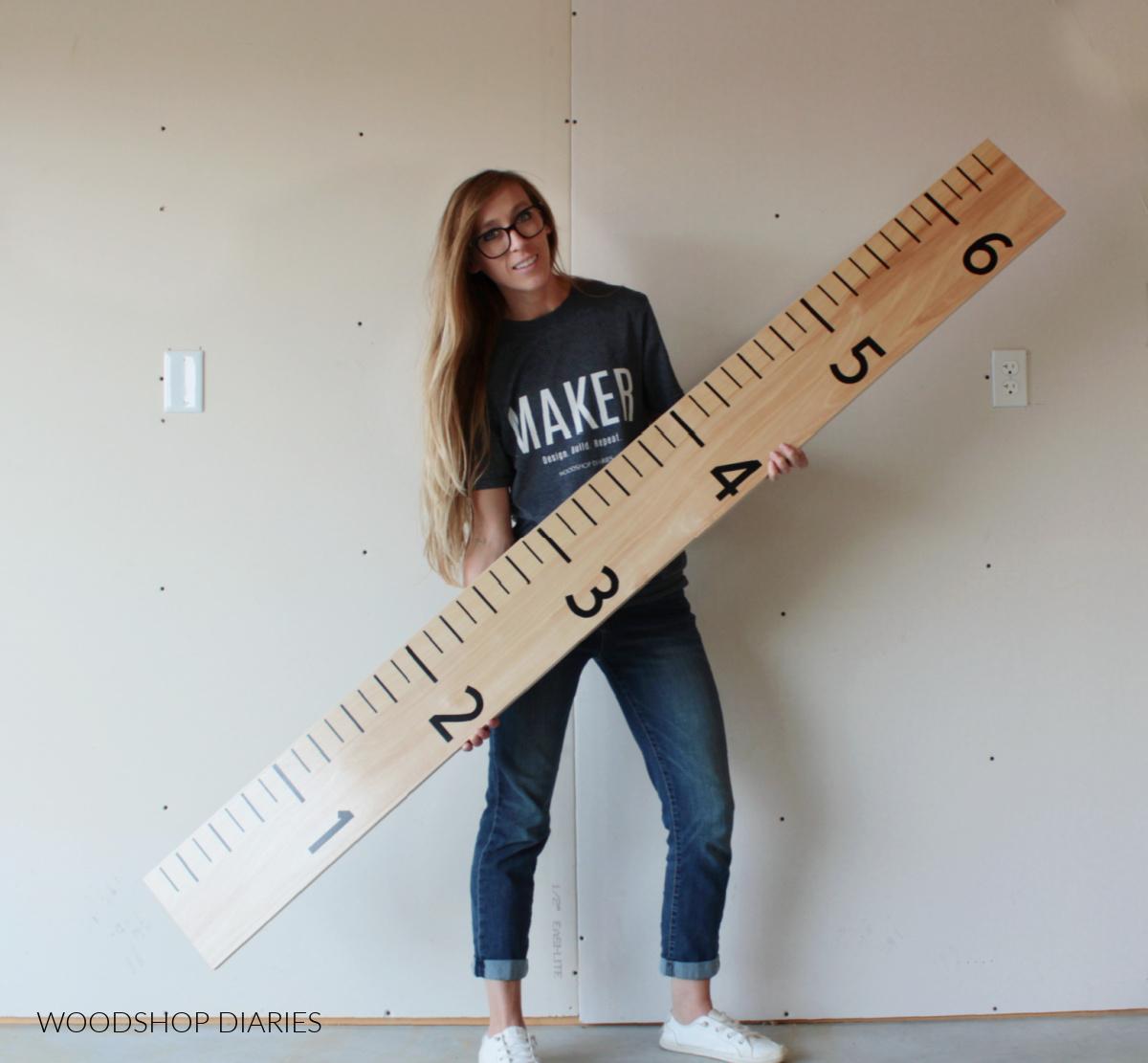Shara Woodshop Diaries holding life size ruler board