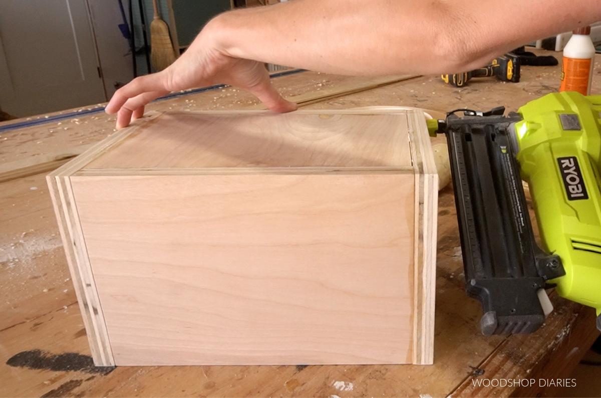 Using nail gun to secure bottom panel through sides