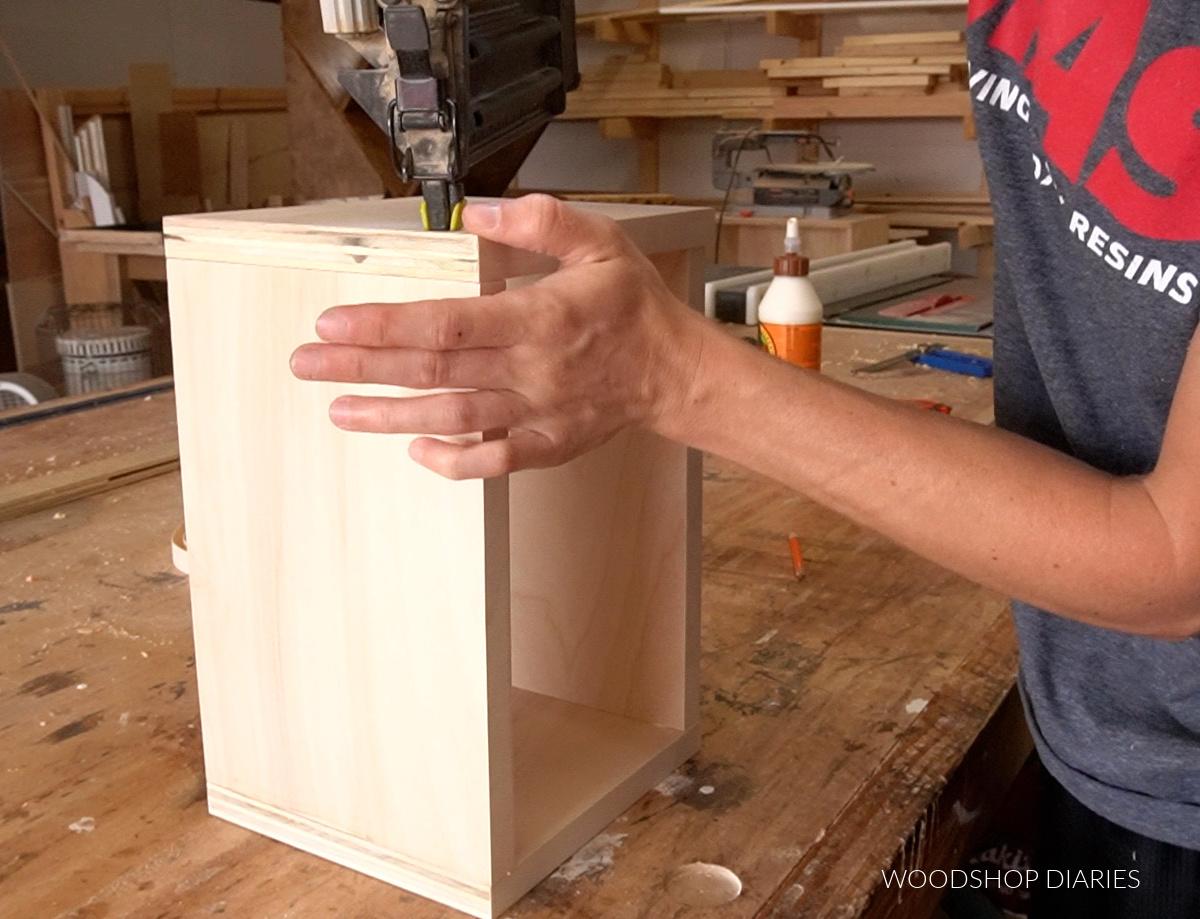 Shara using nail gun to glue and nail keepsake box together
