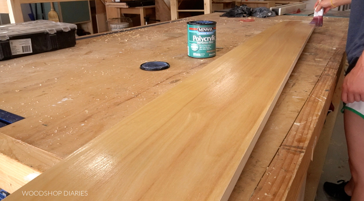 Clear coat being brushed onto board on workbench
