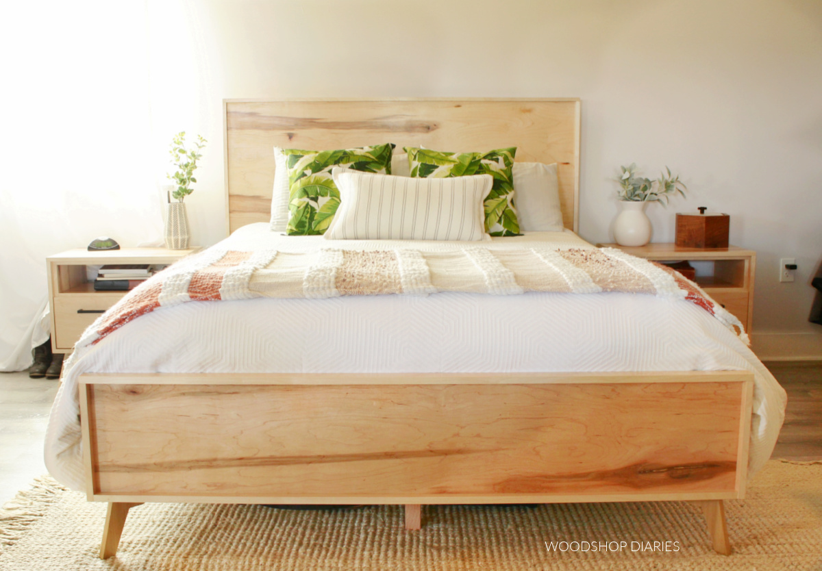 Finished plywood mid century modern bed with white comforter and matching nightstands