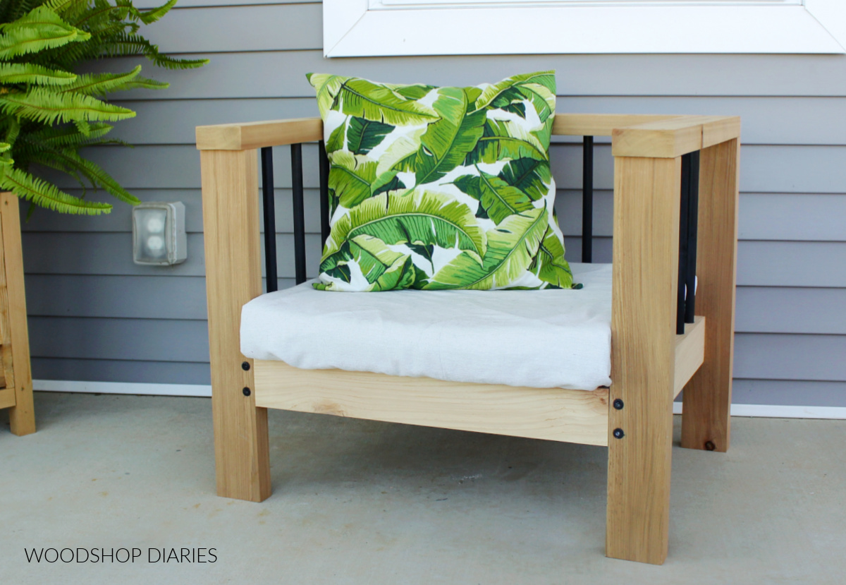 Simple modern DIY outdoor chair made from cedar and wood dowels sitting on front porch with cushion and pillow