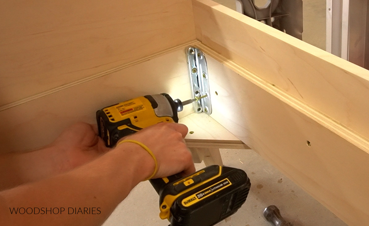 Screwing brackets into corners of bed between footboard and side rails