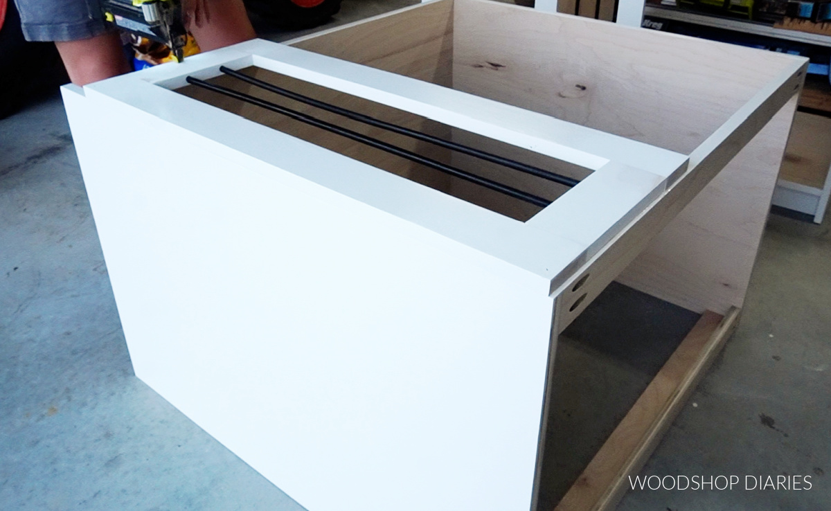 Shara Woodshop Diaries brad nailing face frame onto wooden dog crate cabinet